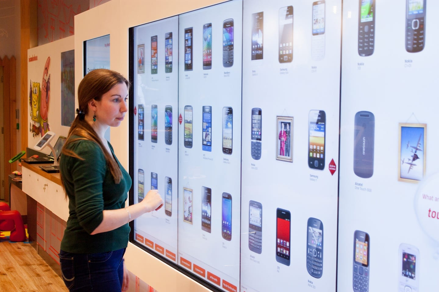 woman browsing products using an interactive touch wall display